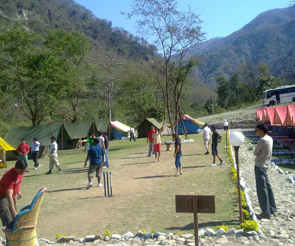 A group playing cricket as a activity in camping